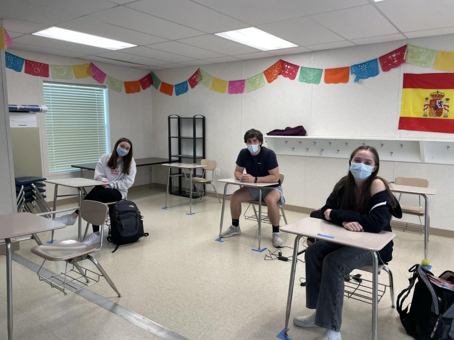 Three seniors, including Olivia Eisenberg (left), sit in a Spanish classrooms. They are the only students for that class who are learning in-person that week.