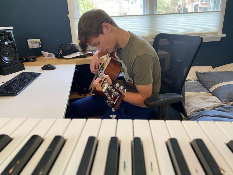 Junior Ian Sincevich strums his guitar while creating a beat in his house. Guitars and keyboards are two common instruments incorporated into modern beats.