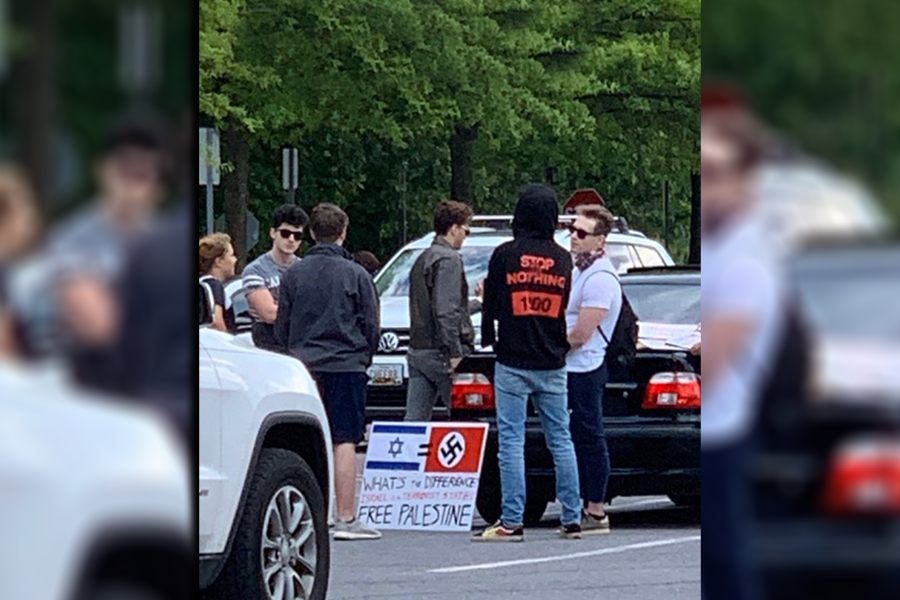 A+group+of+Whitman+students+encountered+men+with+an+anti-Israel+poster+in+the+school%E2%80%99s+parking+lot+Tuesday+evening.+A+photo+of+the+sign+circulated+among+Whitman+students%2C+many+of+whom+condemned+the+poster%E2%80%99s+rhetoric+on+Instagram.