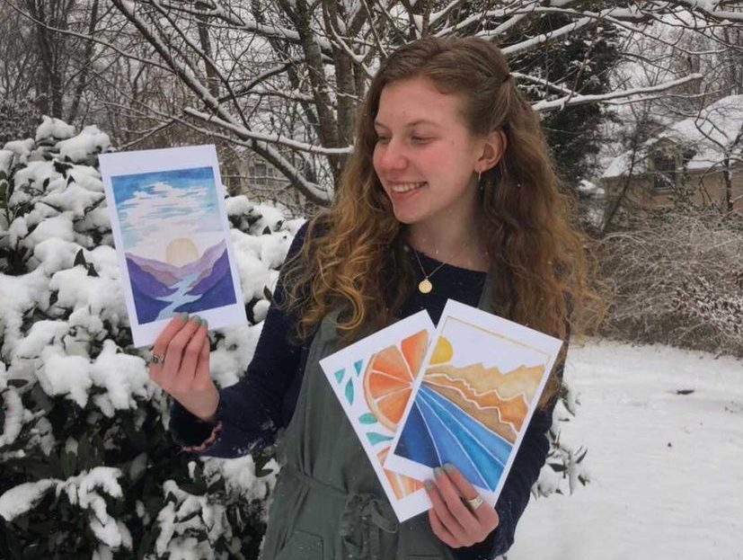 Lila Wohl stands in her backyard holding three greeting cards that she made for her Etsy shop, ArtsForAlzheimers.