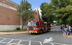 A fire truck arrives at Whitman as students and staff gather outside. Due to a gasoline-like smell in the band room, administrators initiated an evacuation of the school around 4 p.m.
